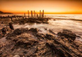 Обои пейзаж, океан, камни, пляж, утро, рассвет, сваи