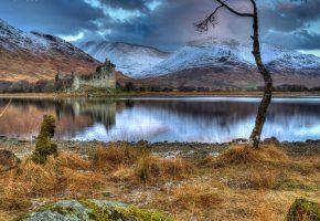 Обои замок, развалины, озеро, горы, берег, камни, трава, дерево, снег, тучи, пасмурно